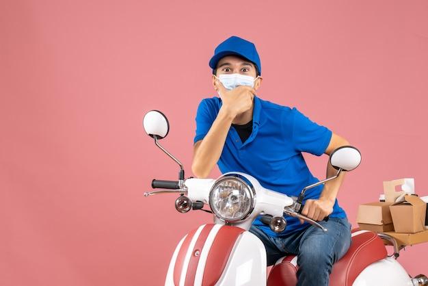 Vista frontal do mensageiro com máscara médica usando chapéu, sentado na scooter e olhando para algo com expressão facial de surpresa em fundo de pêssego pastel