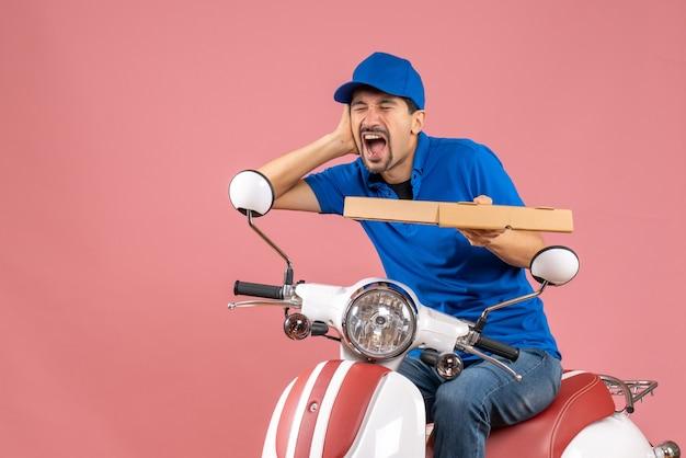 Vista frontal do mensageiro de chapéu sentado na scooter, sofrendo de dor de ouvido, em um fundo cor de pêssego.