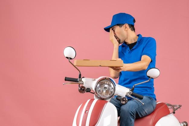 Vista frontal do mensageiro de chapéu sentado na scooter, sofrendo de dor em um fundo cor de pêssego.