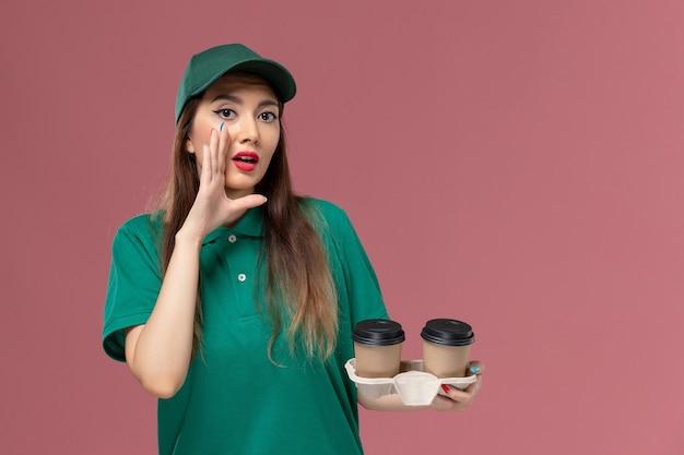 Vista frontal do mensageiro de uniforme verde e capa segurando copos de café de entrega sussurrando na parede rosa empresa serviço trabalho uniforme entregador trabalhador feminino trabalho feminino