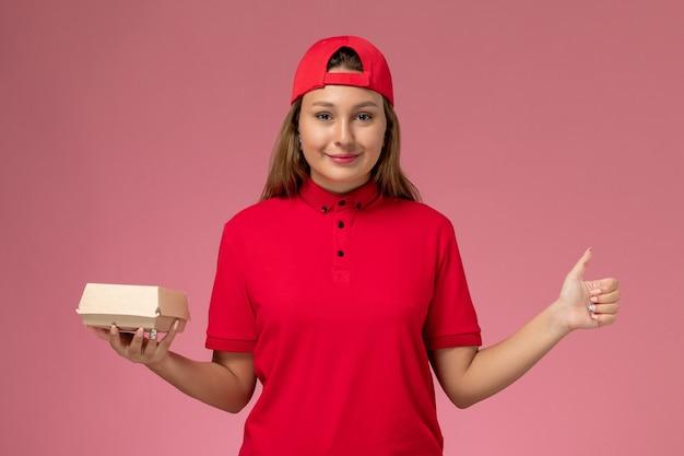 Vista frontal do mensageiro de uniforme vermelho e capa segurando um pacote de comida de entrega em fundo rosa.