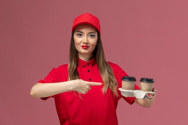 Vista frontal do mensageiro de uniforme vermelho segurando xícaras de café marrom no fundo rosa claro serviço entrega uniforme trabalhador trabalho feminino senhora empresa