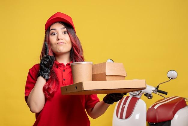 Vista frontal do mensageiro feminino com entrega de comida e sobremesa na parede amarela