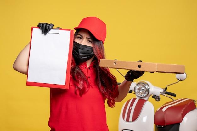 Vista frontal do mensageiro feminino com máscara com caixa de entrega de comida e nota de arquivo na parede amarela
