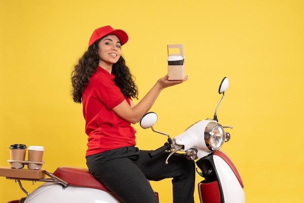 Vista frontal do mensageiro feminino em bicicleta para entrega de café em fundo amarelo serviço entrega uniforme trabalho trabalhador trabalho mulher