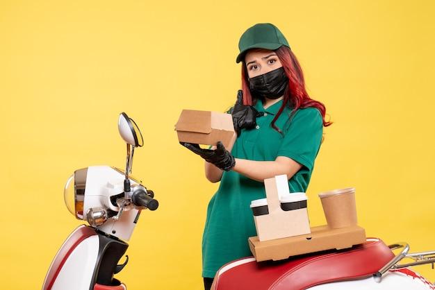 Vista frontal do mensageiro feminino na máscara com entrega de café e comida na parede amarela