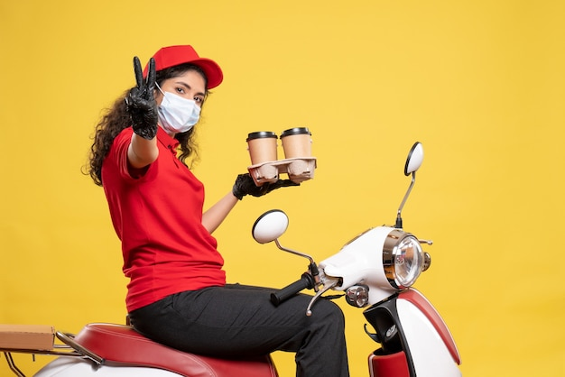 Vista frontal do mensageiro feminino na máscara na bicicleta com xícaras de café no fundo amarelo trabalhador serviço pandemia uniforme mulher entrega covid-