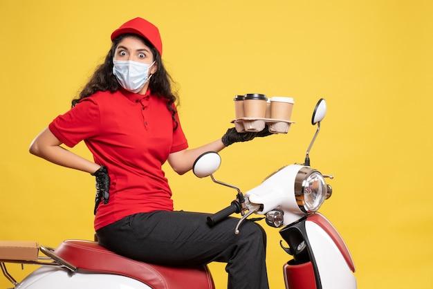 Vista frontal do mensageiro feminino na máscara na bicicleta com xícaras de café no fundo amarelo trabalhador serviço pandemia uniforme trabalho mulher covid-