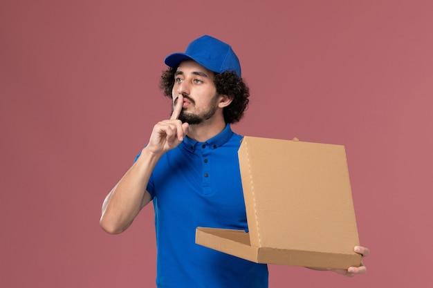 Vista frontal do mensageiro masculino com boné de uniforme azul e caixa de comida aberta nas mãos na parede rosa claro