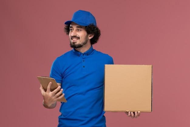 Vista frontal do mensageiro masculino com boné uniforme azul, bloco de notas e caixa de comida nas mãos na parede rosa