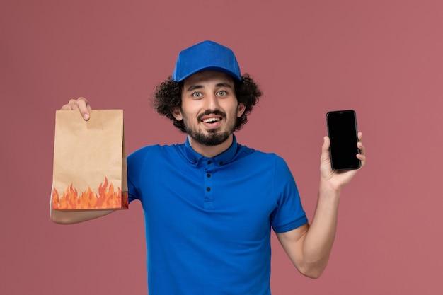 Vista frontal do mensageiro masculino com boné uniforme azul com smartphone e pacote de entrega de comida nas mãos na parede rosa