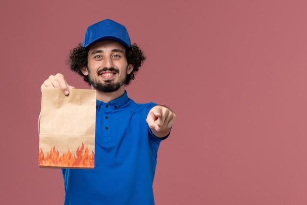 Vista frontal do mensageiro masculino com boné uniforme azul e pacote de comida de papel nas mãos na parede rosa claro