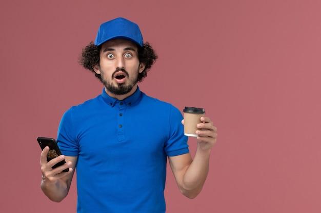 Vista frontal do mensageiro masculino com uniforme azul e boné com xícara de café de entrega e smartphone nas mãos na parede rosa
