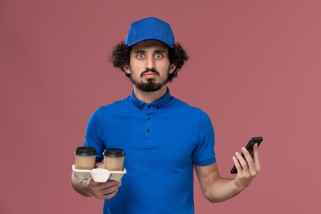 Vista frontal do mensageiro masculino com uniforme azul e boné com xícaras de café para entrega e telefone do trabalho nas mãos na parede rosa