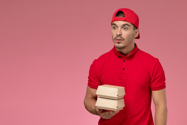 Vista frontal do mensageiro masculino de uniforme vermelho e boné segurando um pequeno pacote de entrega na parede rosa claro