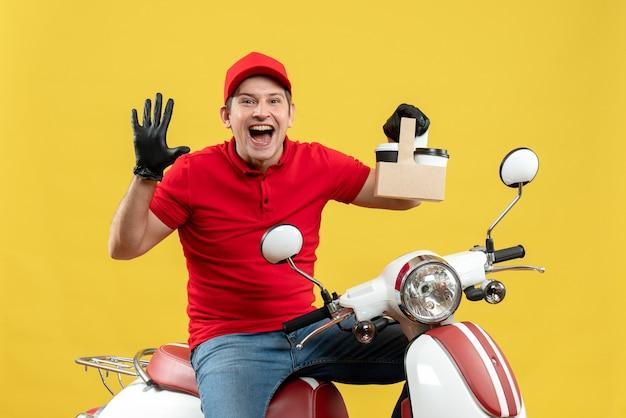 Vista frontal do mensageiro sorridente usando blusa vermelha e luvas de chapéu na máscara médica, entregando pedidos sentado na scooter segurando pedidos mostrando cinco