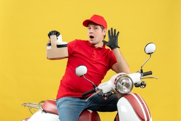 Vista frontal do mensageiro surpreso com blusa vermelha e luvas de chapéu na máscara médica, entregando pedidos sentado na scooter segurando pedidos mostrando cinco