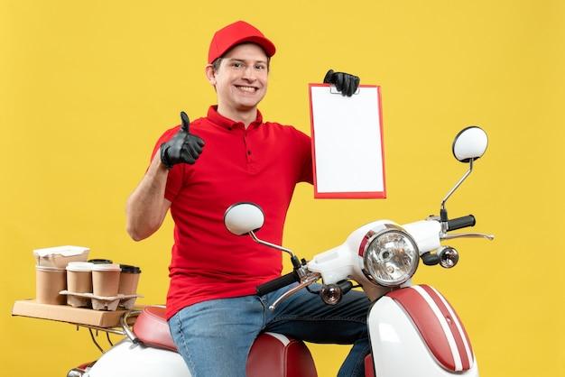 Vista frontal do mensageiro usando blusa vermelha e luvas de chapéu na máscara médica, entregando o pedido, sentado na scooter, segurando o documento, fazendo um gesto de ok