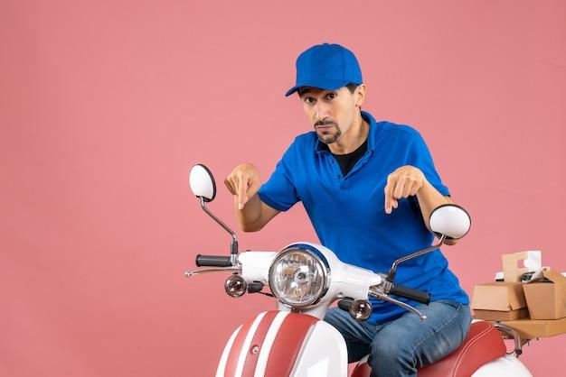 Vista frontal do mensageiro usando chapéu, sentado na scooter e apontando para baixo sobre um fundo cor de pêssego
