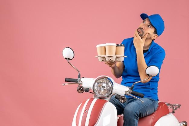 Vista frontal do mensageiro usando um chapéu sentado na scooter, pensando profundamente sobre um fundo cor de pêssego.