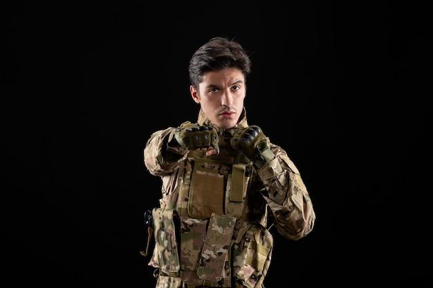 Vista frontal do militar de uniforme e lutador posa na parede preta