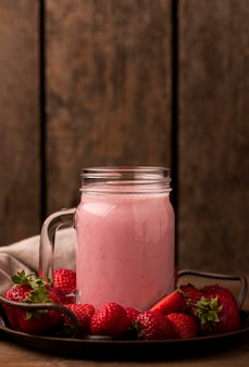 Vista frontal do milkshake de morango com frutas e espaço de cópia