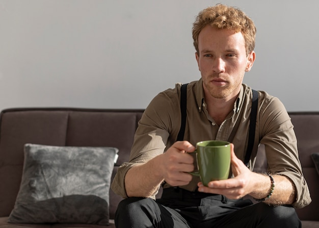 Vista frontal do modo masculino sentado no sofá e bebe café