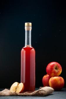Vista frontal do molho de maçã vermelha em uma garrafa com maçãs frescas na superfície escura