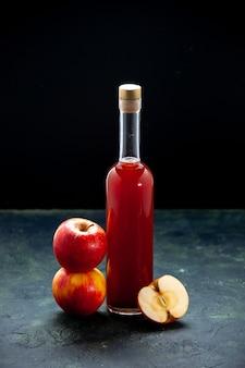Vista frontal do molho de maçã vermelha em uma garrafa em uma superfície escura