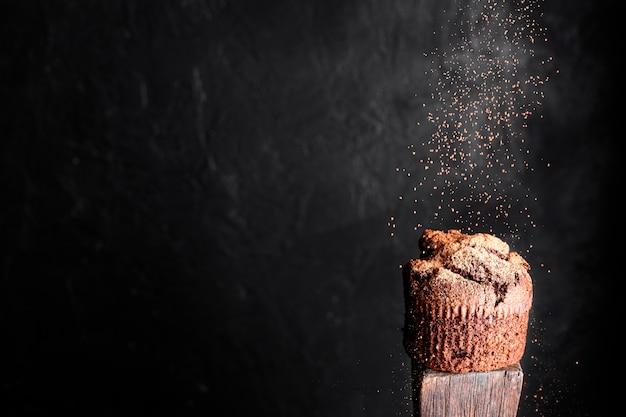 Vista frontal do muffin de chocolate com cacau em pó e copie o espaço