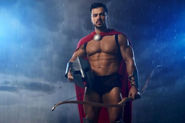 Vista frontal do musculoso espartano barbudo vestindo capa vermelha, segurando o arco e o capacete de ferro enquanto chovia ao ar livre. retrato de homem bonito molhado posando com arma, olhando para a câmera em tempo nublado.