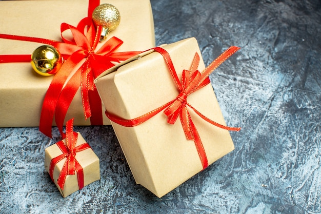 Vista frontal do natal presentes com biscoitos doces no claro-escuro foto do feriado presente de natal ano novo
