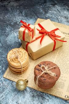 Vista frontal do natal presentes com biscoitos e brinquedos na foto colorida claro-escuro presente ano novo feriado de natal