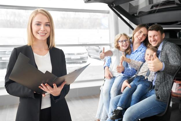 Vista frontal do negociante de carro feminino, mantendo o contrato nas mãos