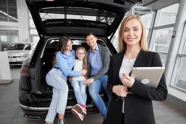 Vista frontal do negociante de carro profissional posando no salão do automóvel