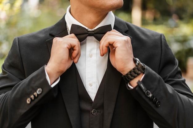 Vista frontal do noivo arrumando a gravata borboleta