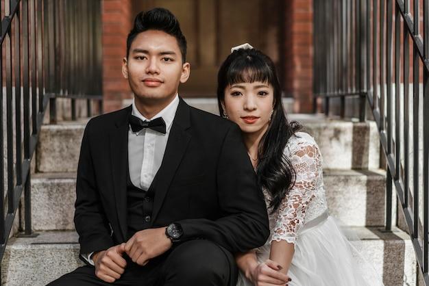 Vista frontal do noivo e da noiva posando juntos nos degraus