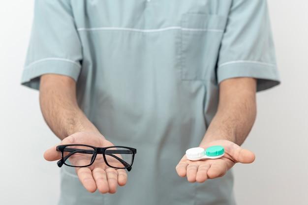 Vista frontal do oftalmologista segurando óculos e lentes de contato