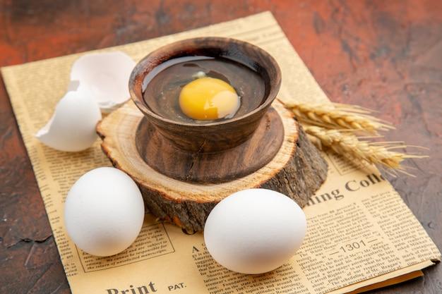 Vista frontal do ovo cru quebrado dentro do prato com outros ovos na superfície escura