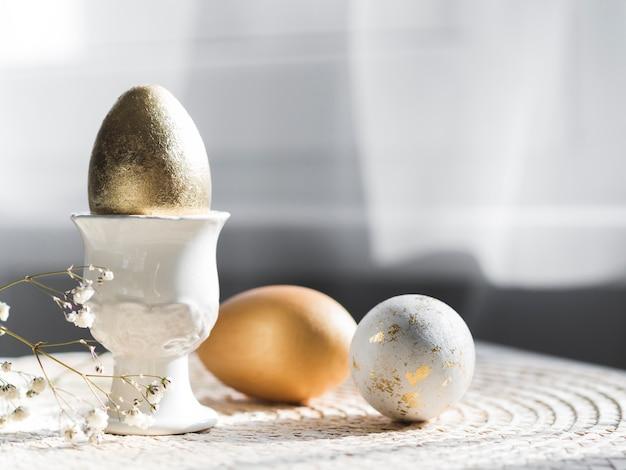Vista frontal do ovo de páscoa dourado no suporte com espaço de cópia