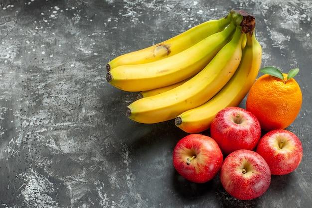 Vista frontal do pacote de bananas frescas de fonte de nutrição orgânica e maçãs vermelhas, uma laranja com haste no lado esquerdo em fundo escuro