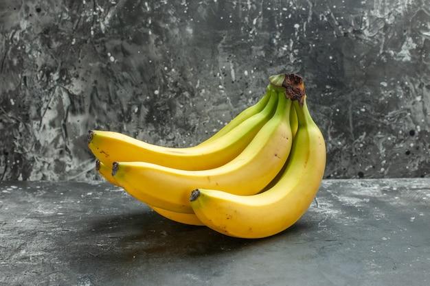 Vista frontal do pacote de bananas frescas de fonte de nutrição orgânica em fundo escuro