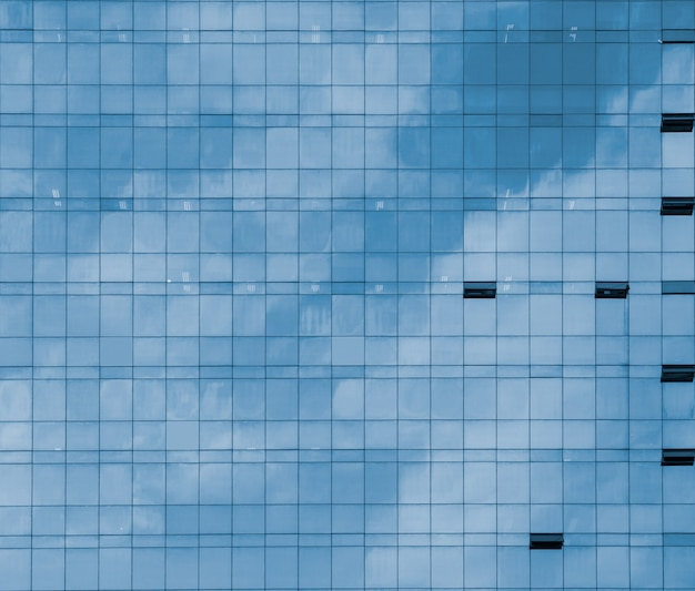 Vista frontal do padrão de janela de vidro do prédio moderno com nuvens e céu azul refletem