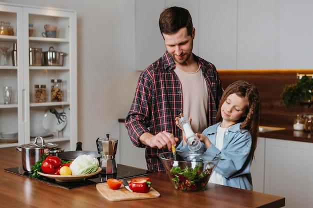 Vista frontal do pai com a filha preparando comida na cozinha