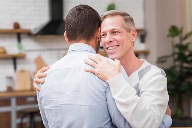 Vista frontal do pai e filho abraçando