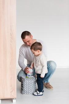 Vista frontal do pai e filho em casa, com espaço de cópia