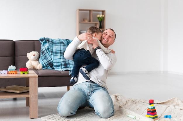 Vista frontal do pai segurando o filho em casa