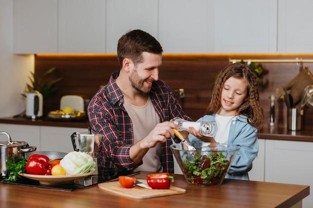 Vista frontal do pai sorridente com a filha preparando comida na cozinha