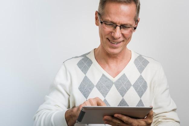 Vista frontal do pai sorridente, olhando no tablet