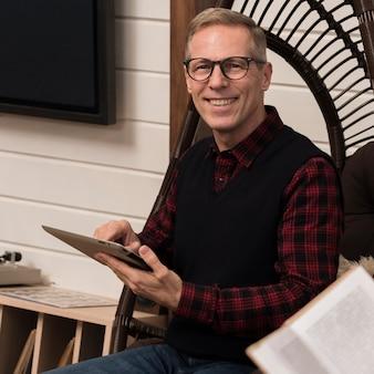 Vista frontal do pai sorridente segurando o tablet